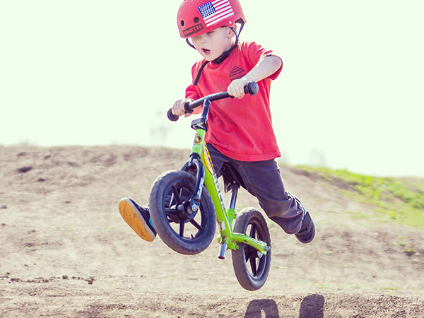 A toddler catches some air on his Strider balance bike.
