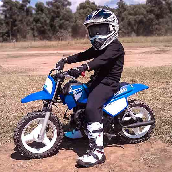 A young dirt bike rider stopping for a quick photo